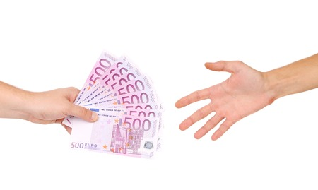 Male hand giving money to a man.  photo