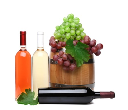 Barrel and bottles of wine and ripe grapes on barrel photo