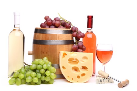 Barrel cheeses bottles and glasses of wine and ripe grapes photo