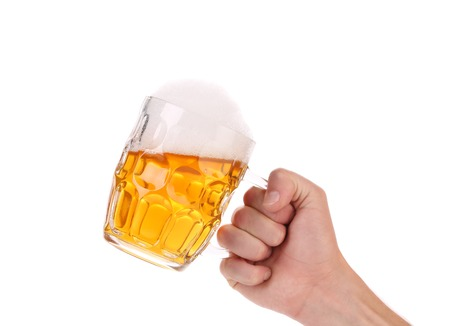 Full beer mug in hand. Isolated on a white background. photo