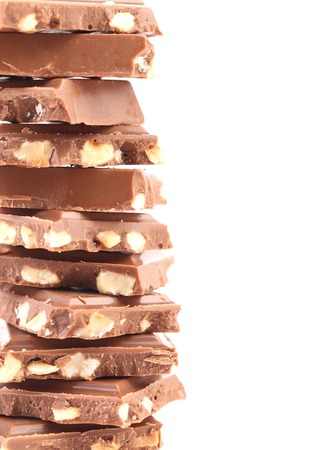Tasty morsel of milk chocolate with nuts. Isolated on a white background. photo