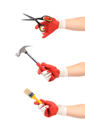 Three hands in protection glove holding hammer scissors and paint brush photo