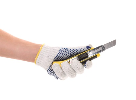 disjoint: Hand holds yellow stationery knife. Isolated on white background.