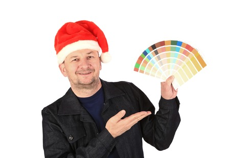 Man in santa's hat with color samples. Isolated on a white background. photo