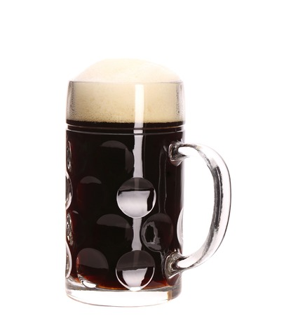 Tall big mug of brown beer with foam. Isolated on a white background. photo