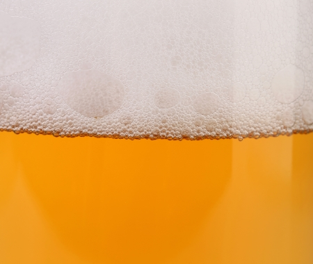 Closeup of beer with foam. Whole background. photo