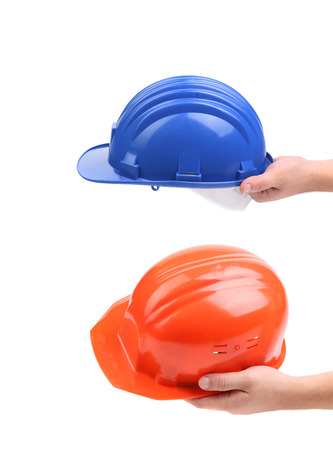 Two hands holding hard hats. Whole background. photo