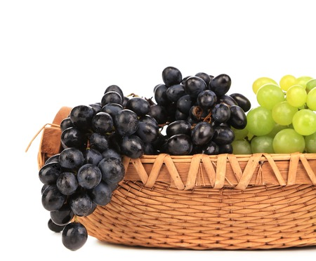 Black and green grapes in basket. Isolated on a white background. photo