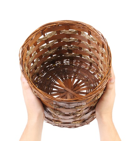 interleaved: Hands hold vintage weave wicker basket. Isolated on a white background