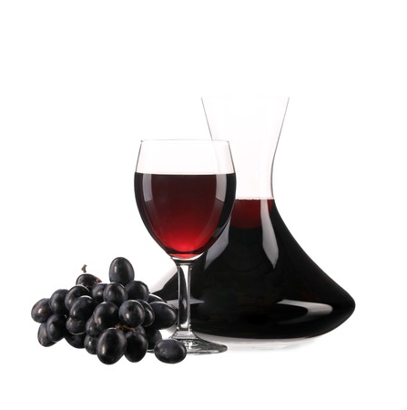 Decanter and glass with red wine and ripe grape Фото со стока