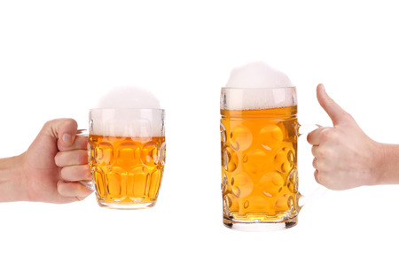 Two full beer mugs in hand  Isolated on a white background  photo