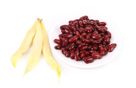 Yellow pods and red beans. Isolated on a white background photo