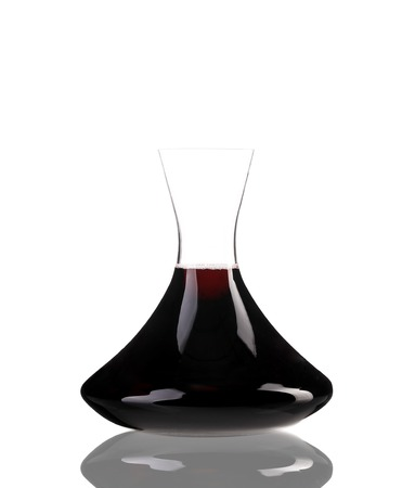 A decanter of red wine with reflection isolated over white background photo
