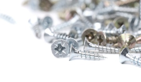 Zinked and anodized screws. Blurred. Isolated on a white background.