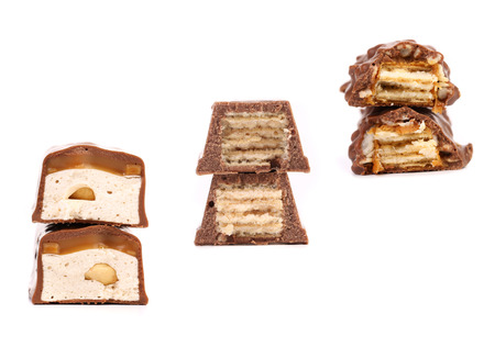 Stacks of broken chocolate bars. Isolated on a white background. photo