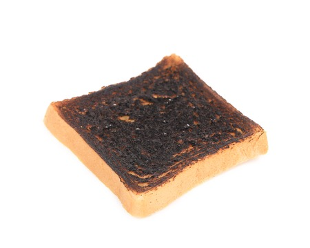 burnt toast: Burnt toast close up. Isolated on a white .