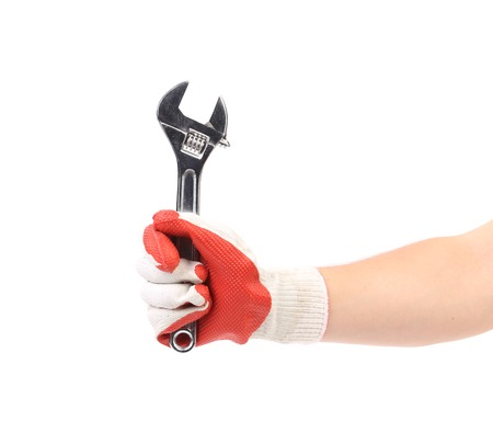 Hand in gloves holding wrench. Isolated on a white background. photo