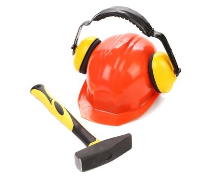 Ear muffs on hard hat and hammer. Isolated on a white background. photo
