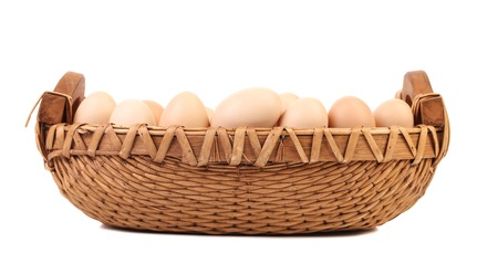Brown eggs in the basket on a white. Isolated on a white background. photo