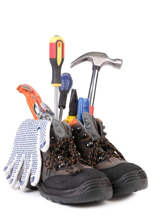 alligator wrench: Building tools and boots composition. Isolated on a white background.