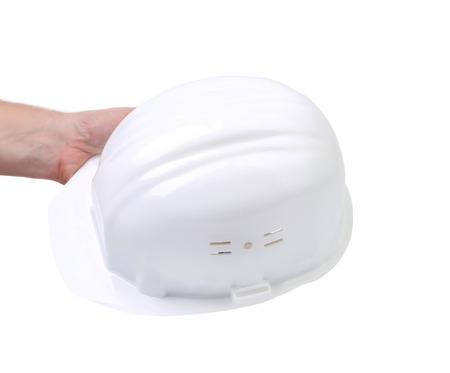 Hand holding white hard hat. Isolated on white background. photo