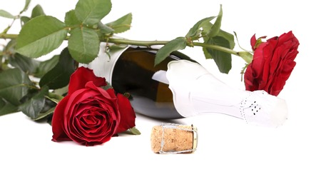 Red rose and a bottle of champagne. Isolated on a white background. photo