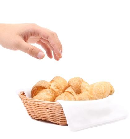 canasta de panes: Alcances de la mano para los croissants en una cesta. Aislado en un fondo blanco. Foto de archivo