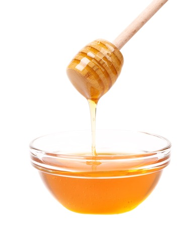Bow of honey and wooden spoon. Isolated on a white background.