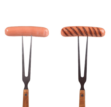 Two grilled sausages on the forks. Isolated on a white background. photo