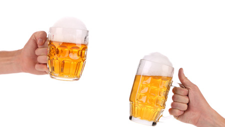 Two full beer mugs in hand. Isolated on a white background. photo