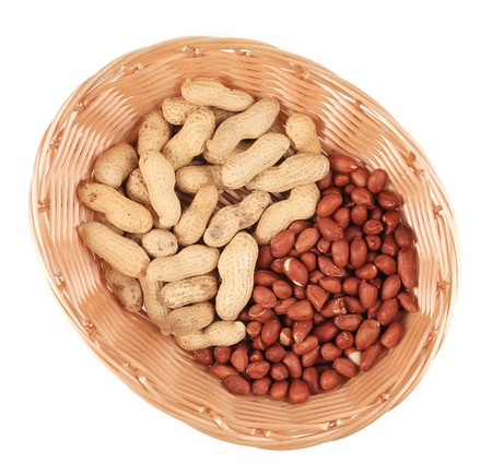hulled: Basket full with peanuts. Isolated on a white background. Stock Photo