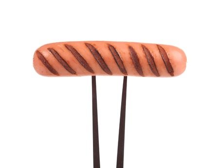 Grilled sausage on a fork. Isolated on a white background. photo