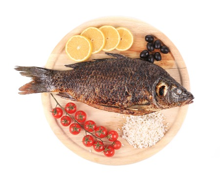 Grilled carp fish with lemon and tomatoes. Isolated on a white background. photo