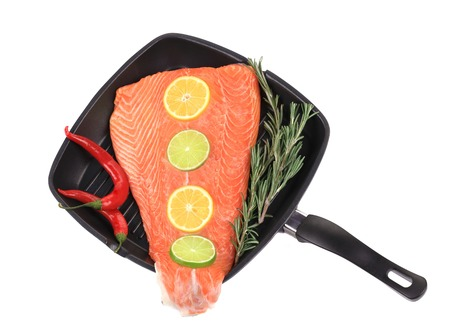 Fresh salmon fillet on a pan. Isolated on a white background. photo