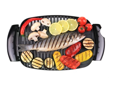 Grilled seabass on grill with vegetables  Isolated on a white  photo