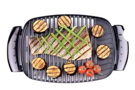 Grilled carp fillet on grill with egg plant. Isolated on a white background. photo