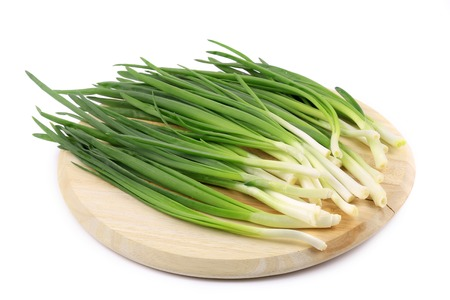 Bunch of green onion on wooden platter. Isolated on a white background. photo