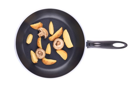 Frying pan with potatoes and mushrooms. Isolated on a white background. photo