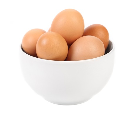 Bowl with brown eggs. Isolated on a white background. photo
