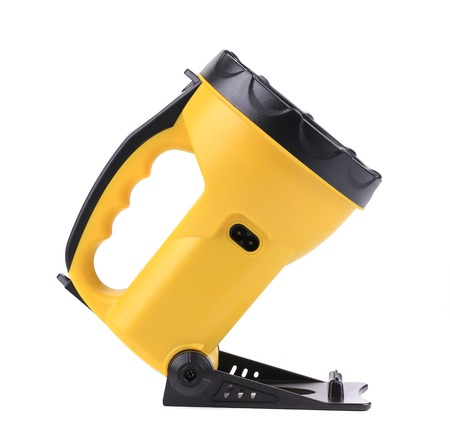 Yellow plastic pocket handle flashlight. Isolated on a white background. photo