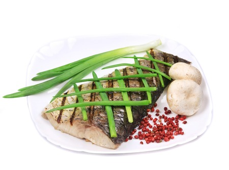 Grilled carp fillet on plate with onion. Isolated on a white background. photo