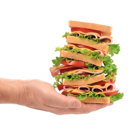 Big fresh sandwich in hands. Isolated on a white background. photo