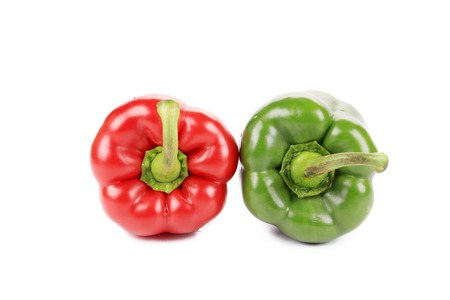 Two red and green peppers close up. Isolated on a white background. photo