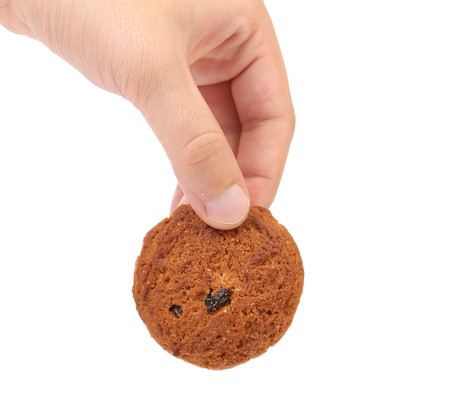 cookie with chocolate pieces in hand. isolated on the white background photo
