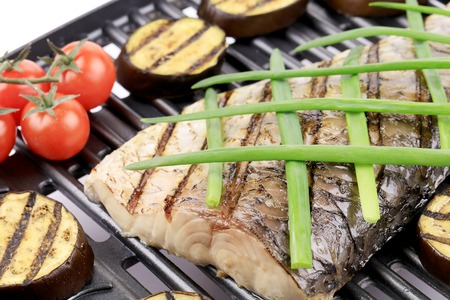 Grilled carp fillet on grill with egg plant. Whole background. photo