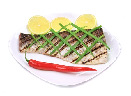 Grilled carp fillet on plate with onion and lemon. Isolated on a white background. photo