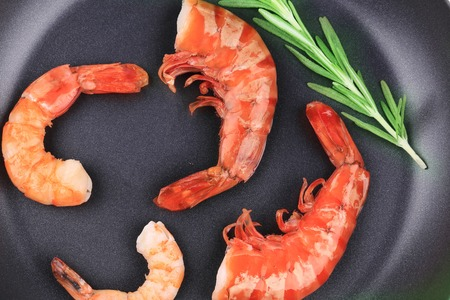 Cooked unshelled shrimps on frying pan. Whole background. photo