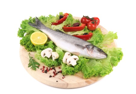 Fresh seabass on platter with lettuce. Isolated on a white background. photo