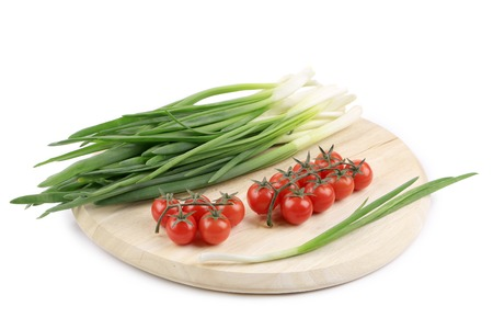 Onions and cherry tomatoes on a wooden board. photo