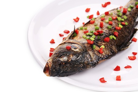 Fried fish with paprika on a white plate. photo